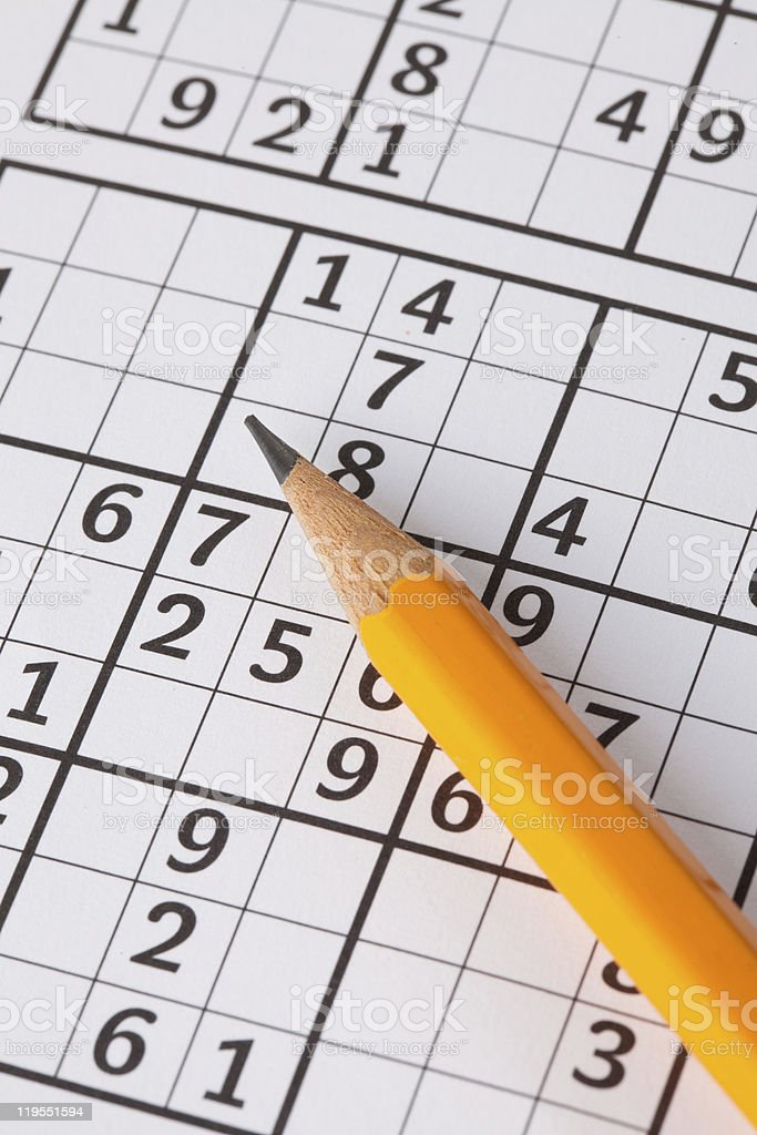 A sudoku game puzzle and a yellow pencil stock photo