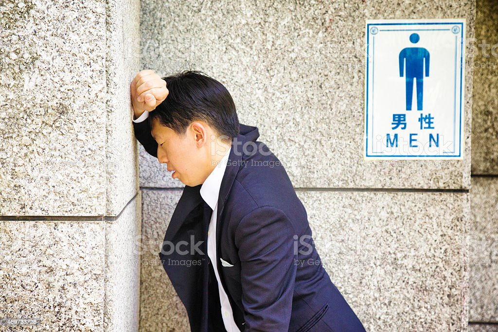Suffering Japanese businessman rests against WC wall feeling sick stock photo