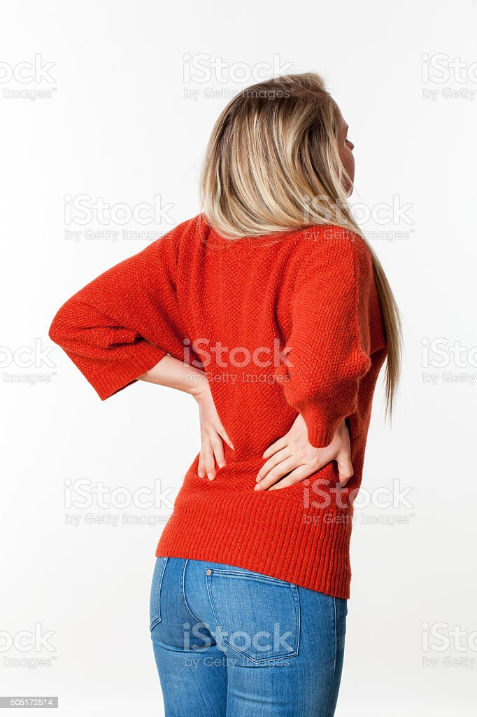 suffering young blond woman touching her lower back vertebrae stock photo