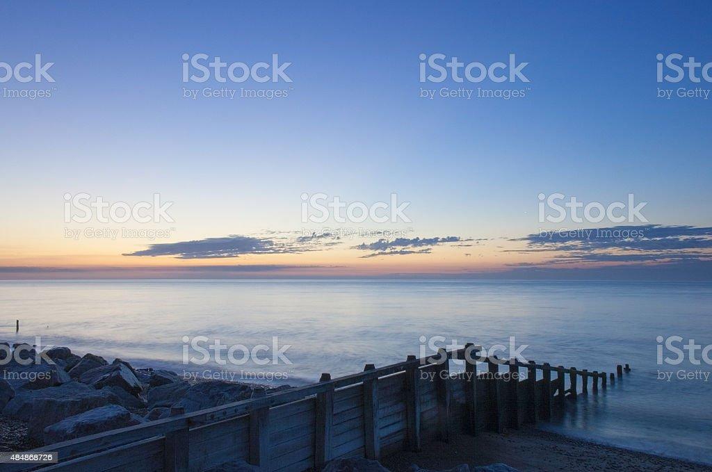 Suffolk coast sunrise, groynes and rocks at dawn, Aldeburgh stock photo
