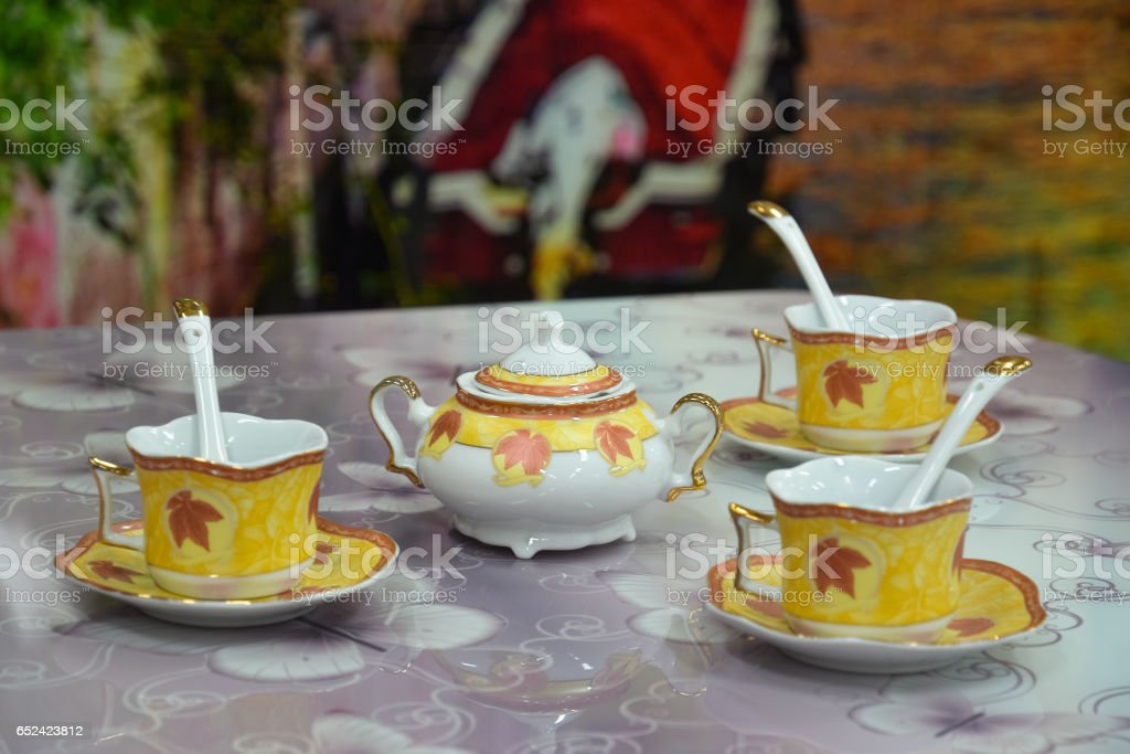 Sugar bowl and three teacups on the table stock photo