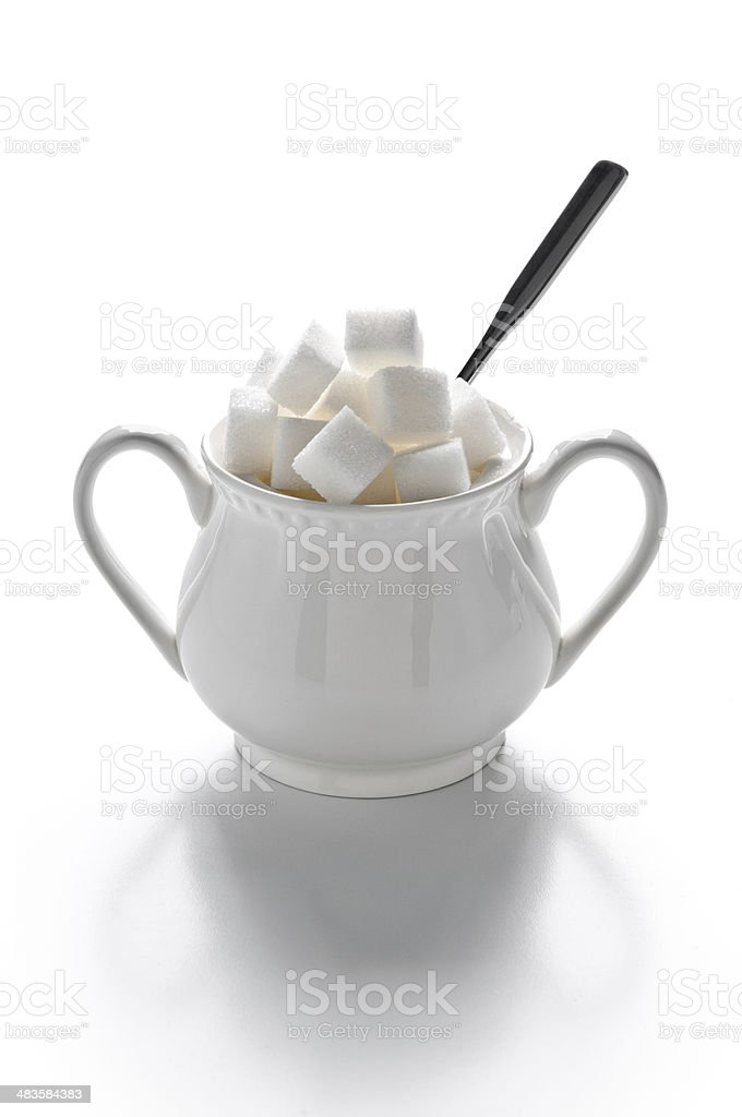 Sugar bowl full of sugar cubes and spoon, isolated on white stock photo