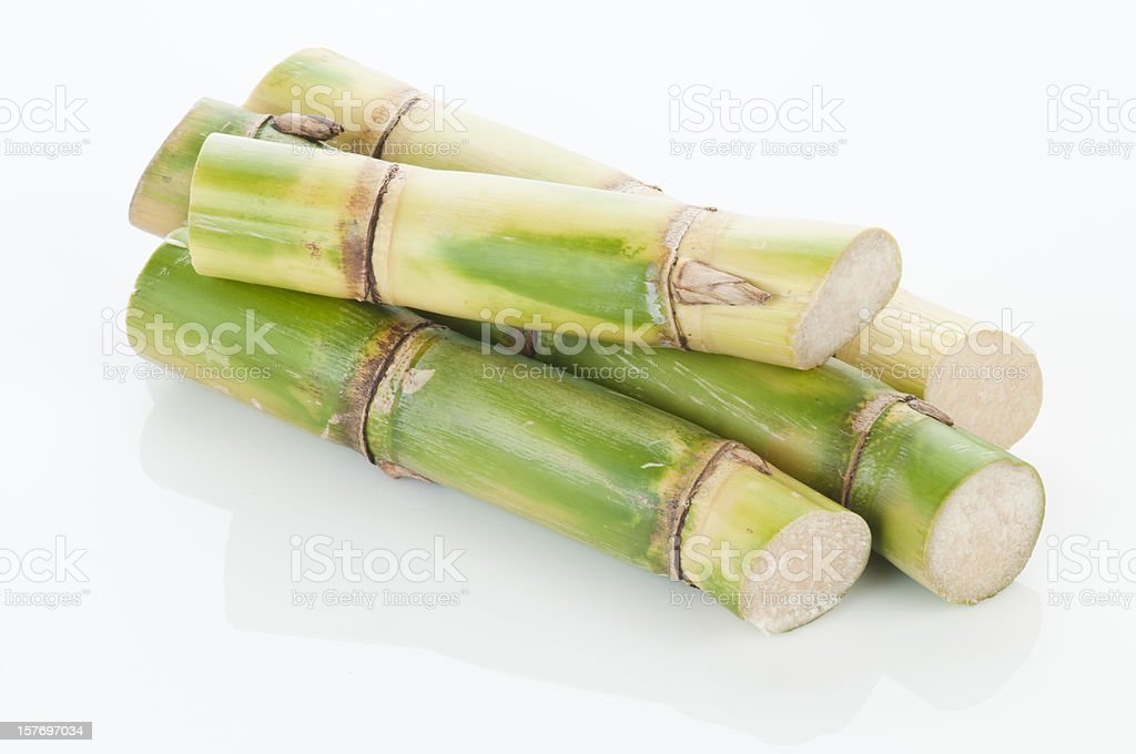 Sugar cane sticks arranged in a pile on white background stock photo