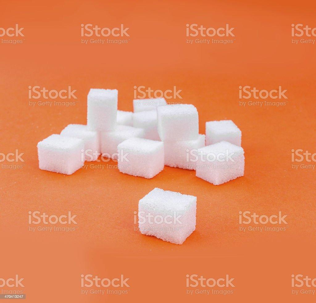 Sugar cube on orange background stock photo