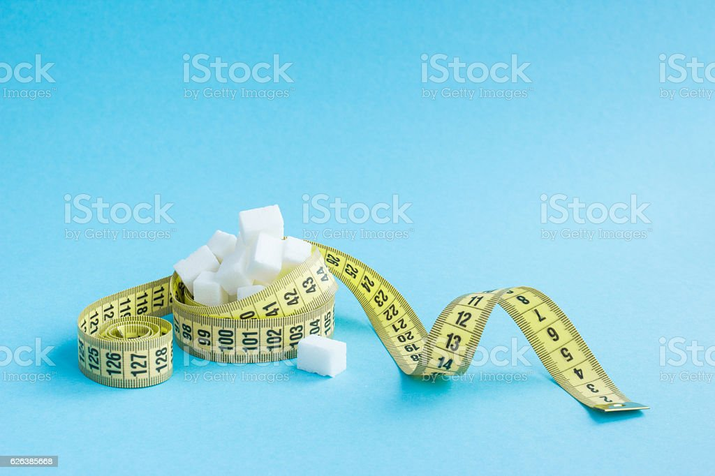 Sugar cubes and Yellow centimeter tape on blue background stock photo