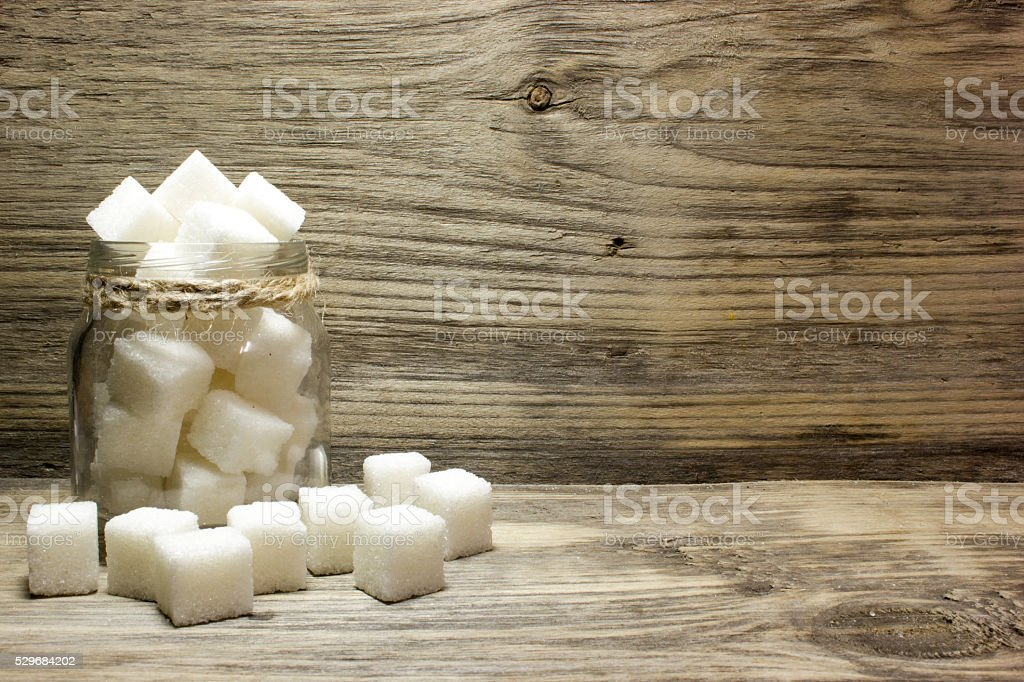 Sugar cubes in glass jar on wooden background stock photo
