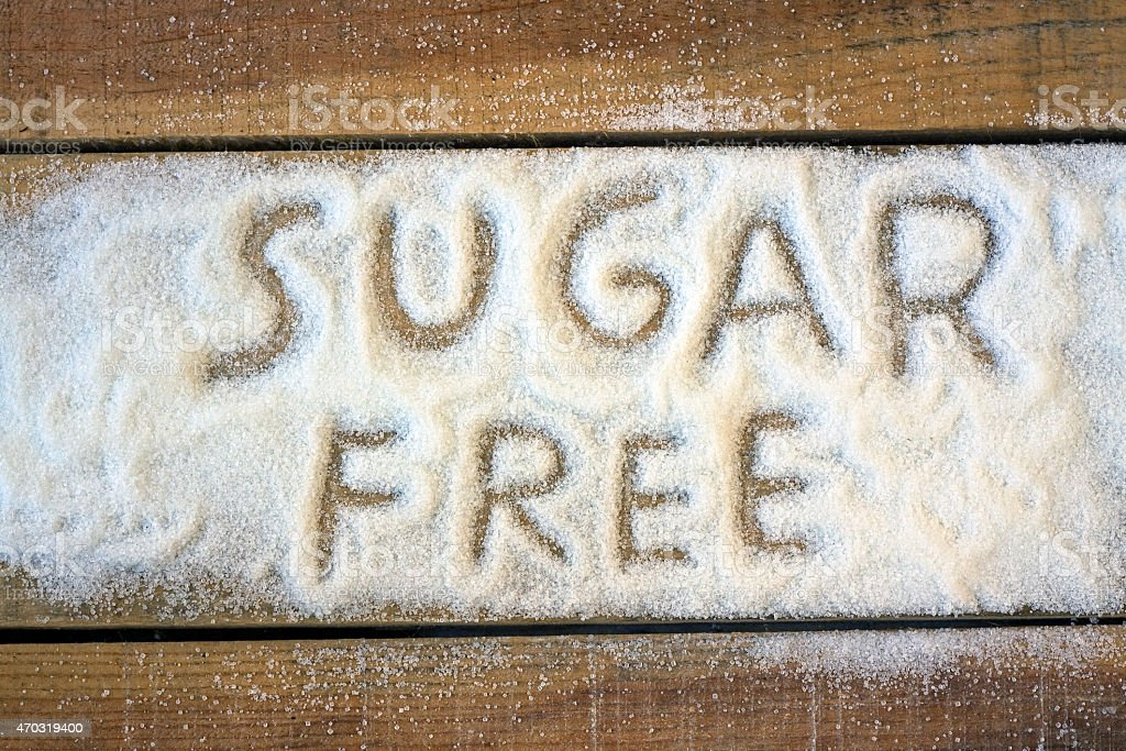 Sugar free written on white sugar on a wooden surface stock photo