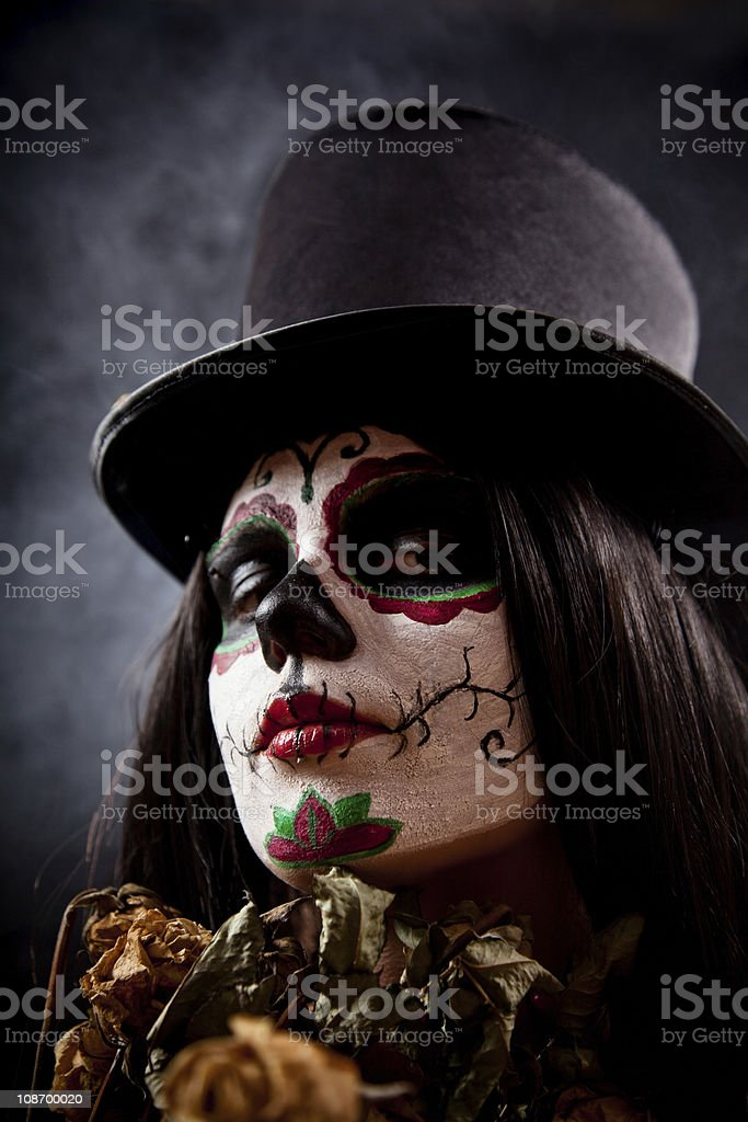 Sugar skull girl in tophat holding dead roses royalty-free stock photo