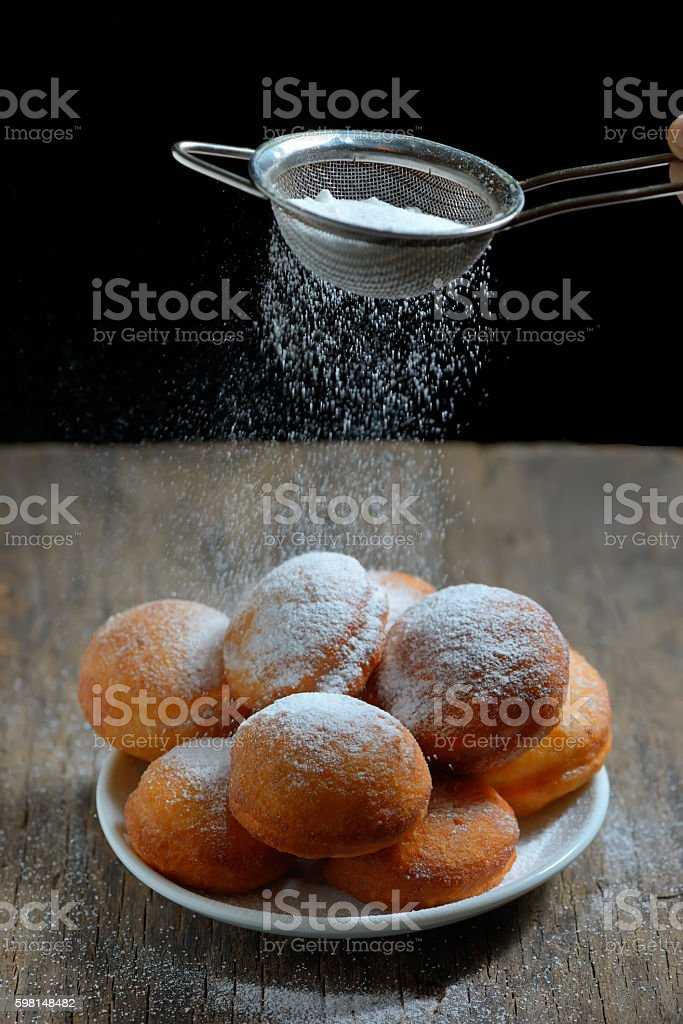 sugar with strainer over donuts stock photo