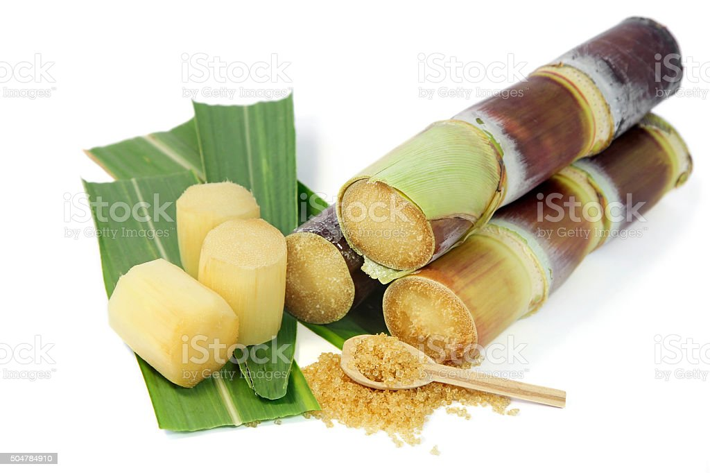 Sugarcane with leaves and granulated brown sugar on white background. stock photo