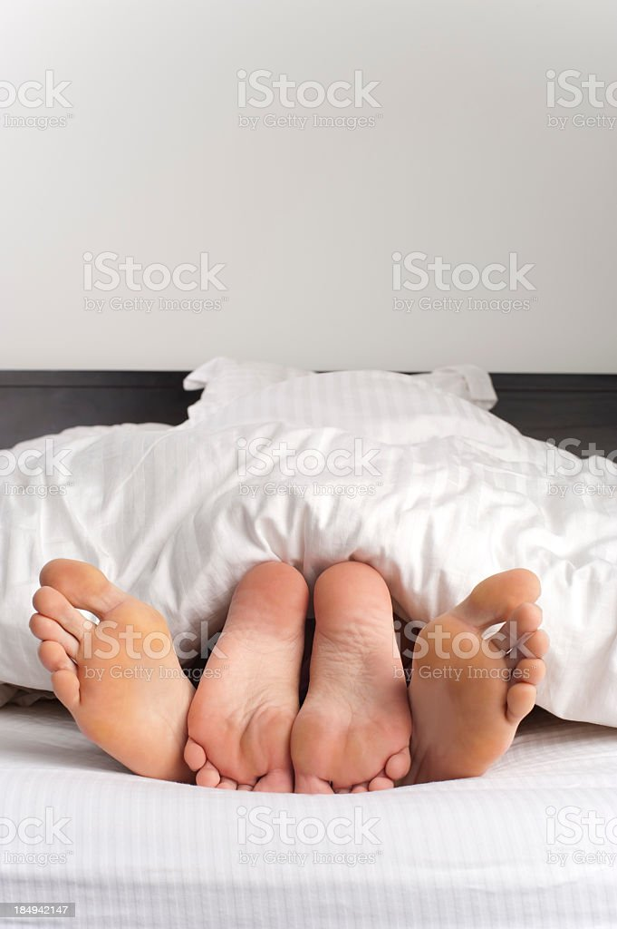 Suggestive photo of a young couple's feet royalty-free stock photo