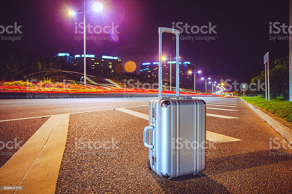 Suitcase beside the highway stock photo