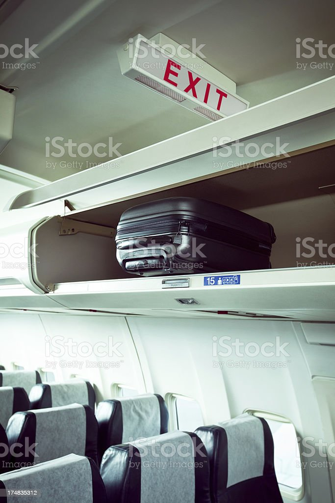 Suitcase in an overhead compartment royalty-free stock photo