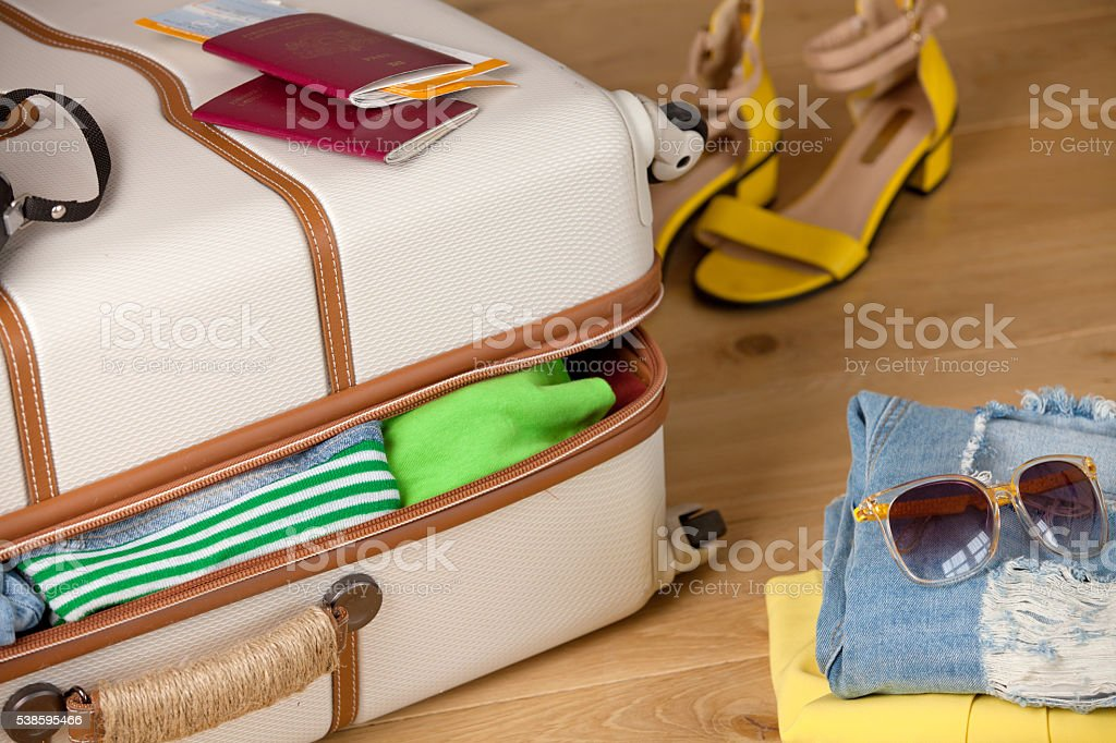 Suitcase on a wooden floor with clothing, tickets, passport and stock photo