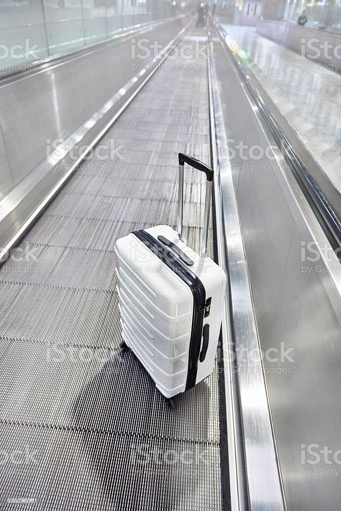Suitcase on moving walkway all metal and shiny stock photo