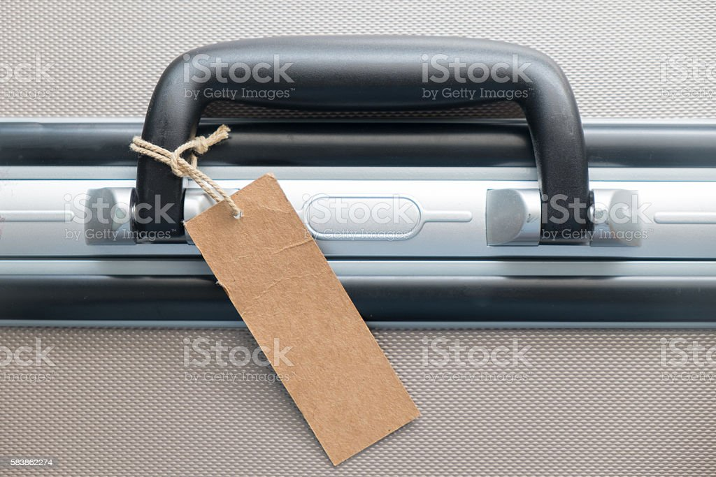 Suitcase with TRAVEL blank luggage tag label or price tag. stock photo