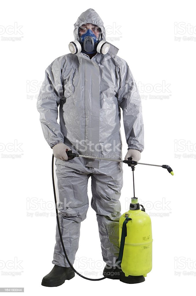 Suited and masked pest control worker carrying sprayer stock photo
