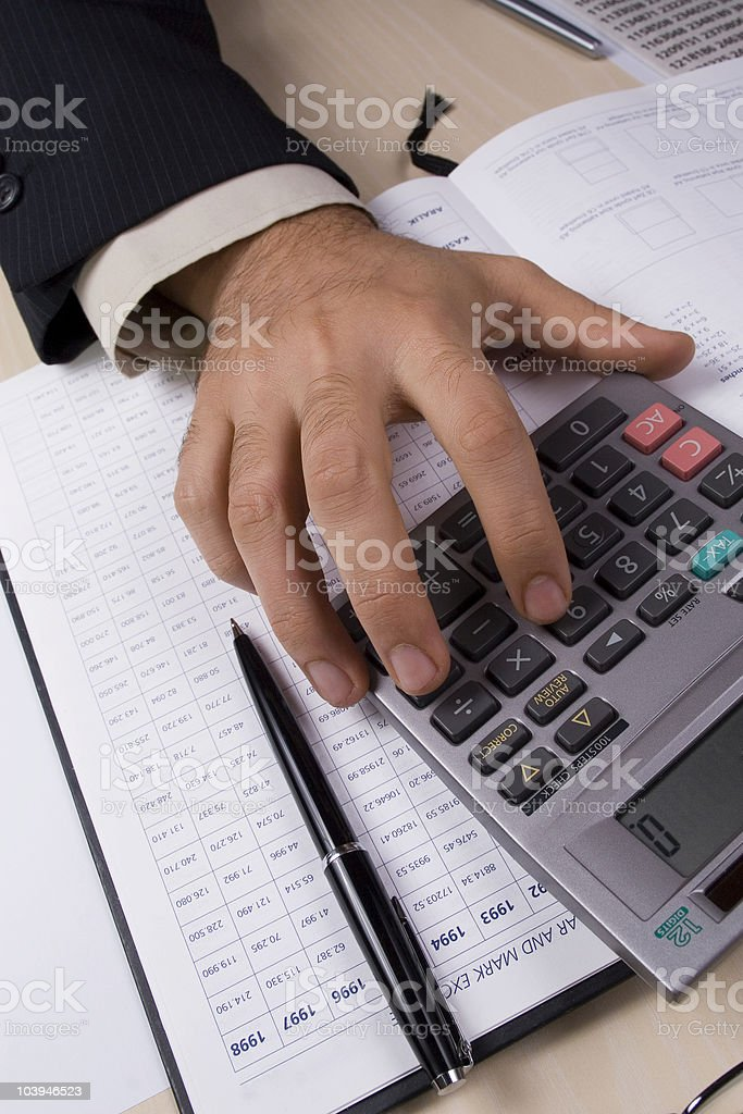 Suited arm using calculator on business finance spreadsheets royalty-free stock photo