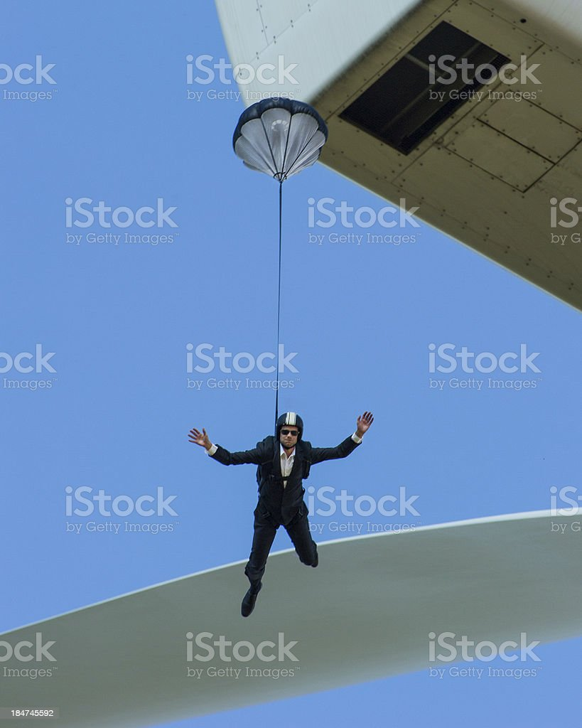 Suited BASE jumper falling from wind turbine stock photo