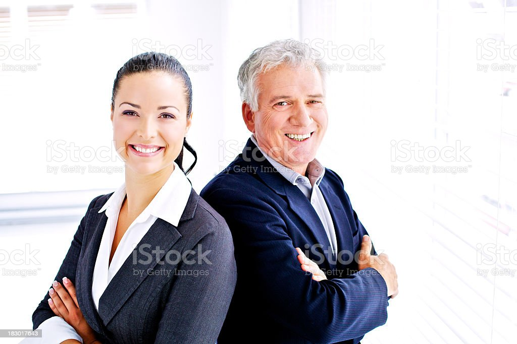 Suited man and woman standing shoulder to shoulder royalty-free stock photo