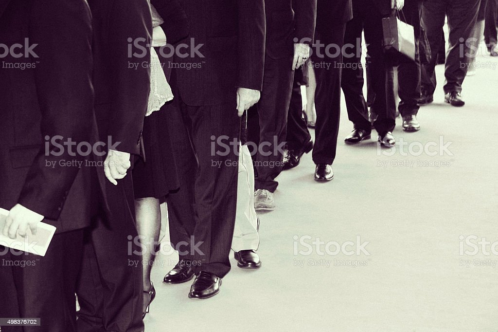 Suits waits in line. Retro black white with noise added stock photo