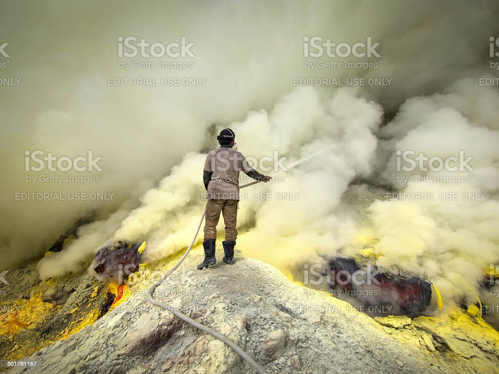 Sulfur Miner Spraying Water Onto Pipes at Kawah Ijen, Indonesia royalty-free stock photo
