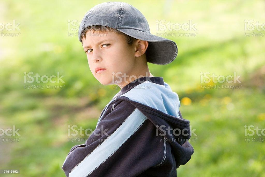 Sulking boy on field stock photo