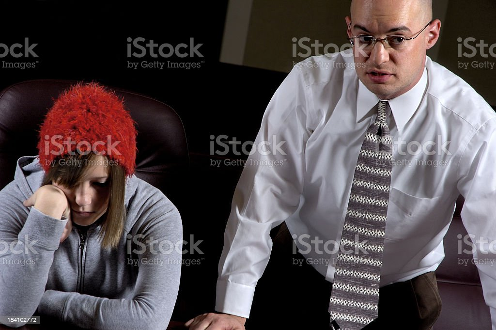 Sulking girl with red hat sitting near man in business suit stock photo