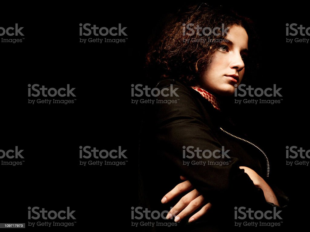 Sullen Woman Crossing Arms on Black Background royalty-free stock photo