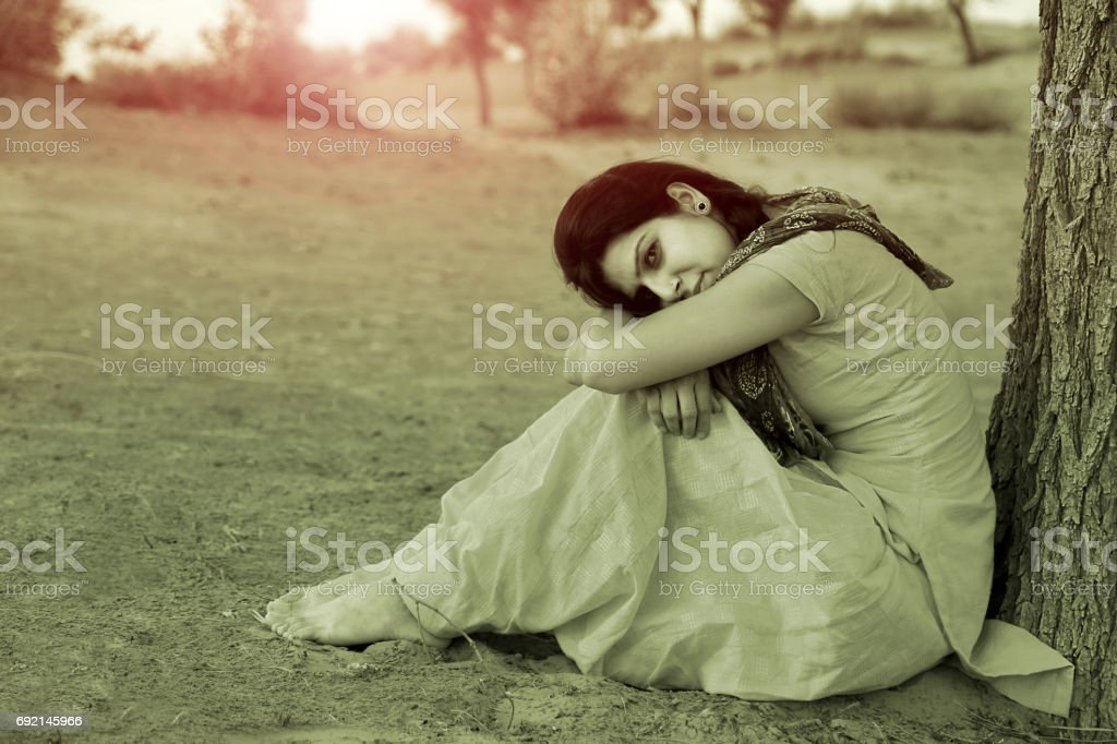 Sullen women near the tree trunk in desert stock photo