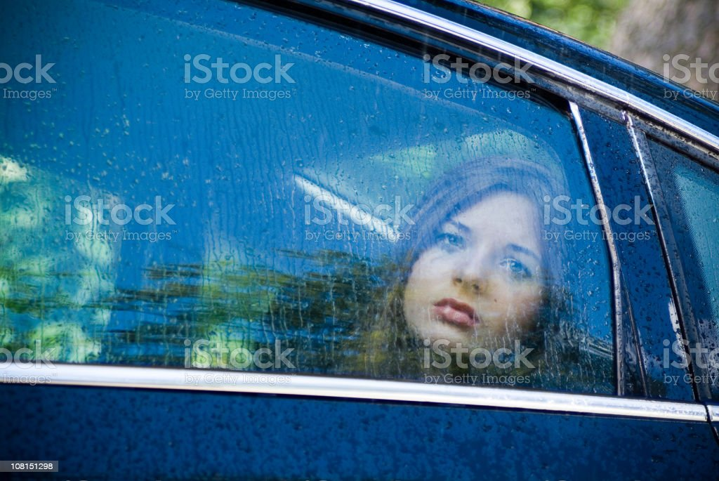 Sullen Young Woman in a Car royalty-free stock photo