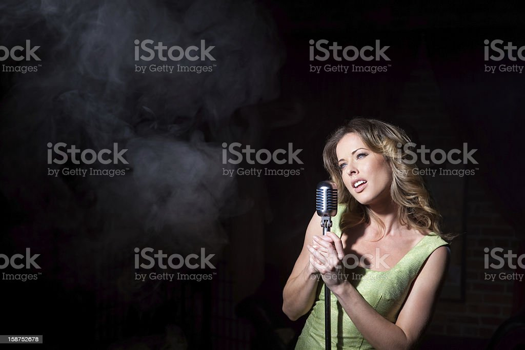 Sultry singer in front of a light beam royalty-free stock photo