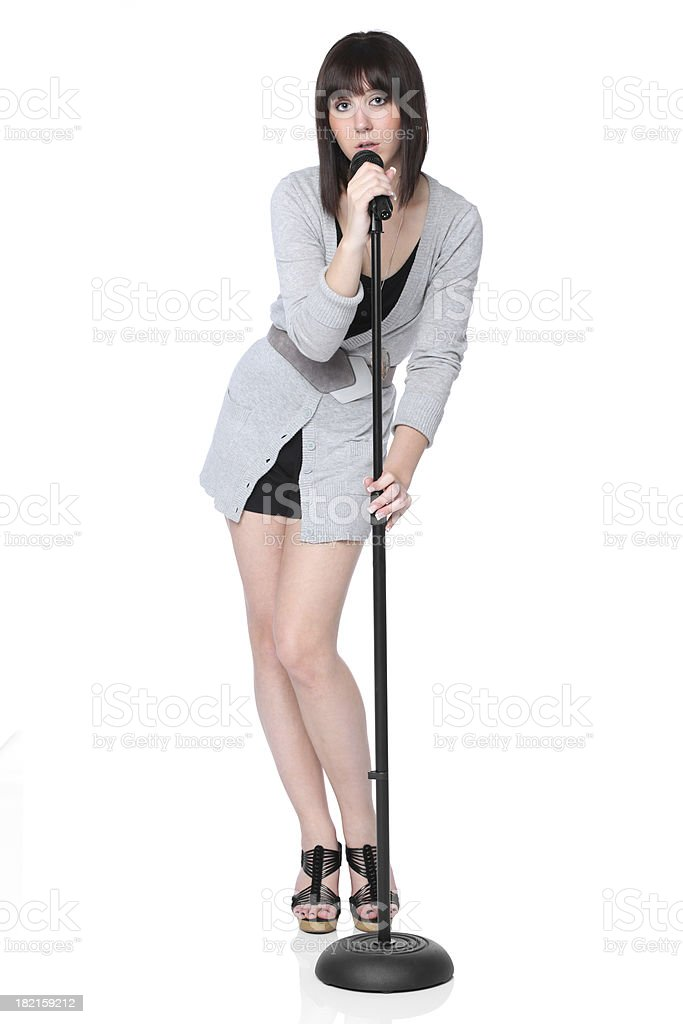 Sultry young woman singing into microphone royalty-free stock photo