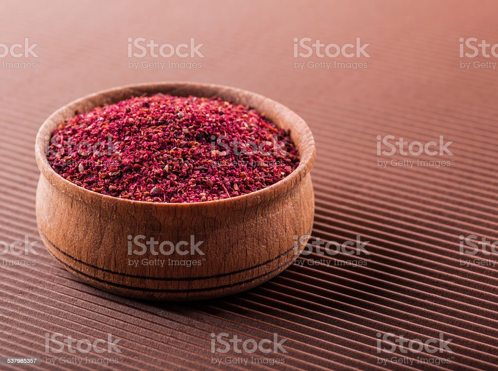 sumac in a wooden bowl stock photo