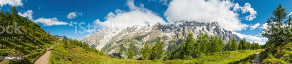 Summer Alpine trail meadows and mountains panorama stock photo