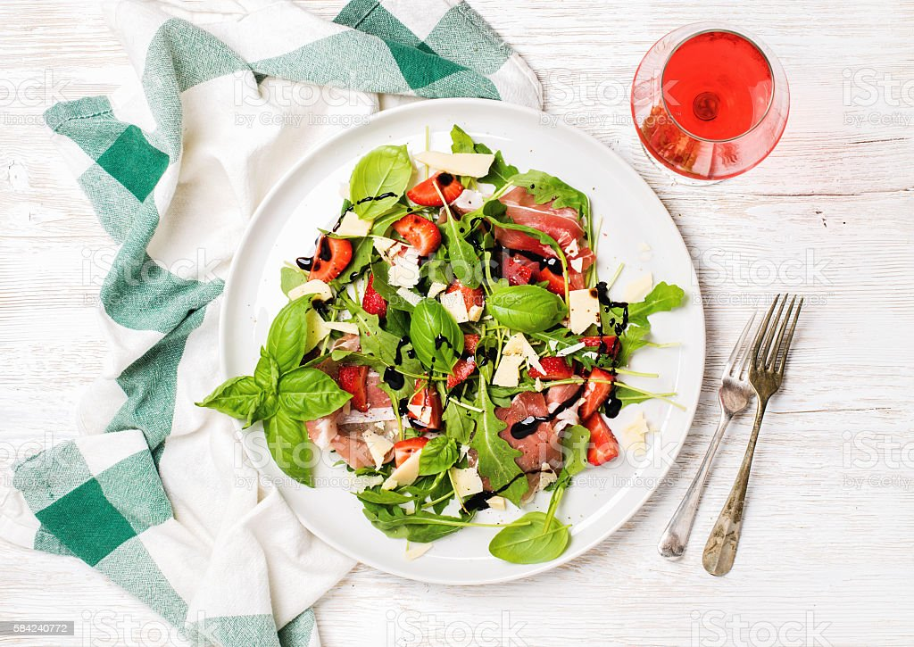 Summer arugula, prosciutto, strawberry salad with glass of rose wine stock photo