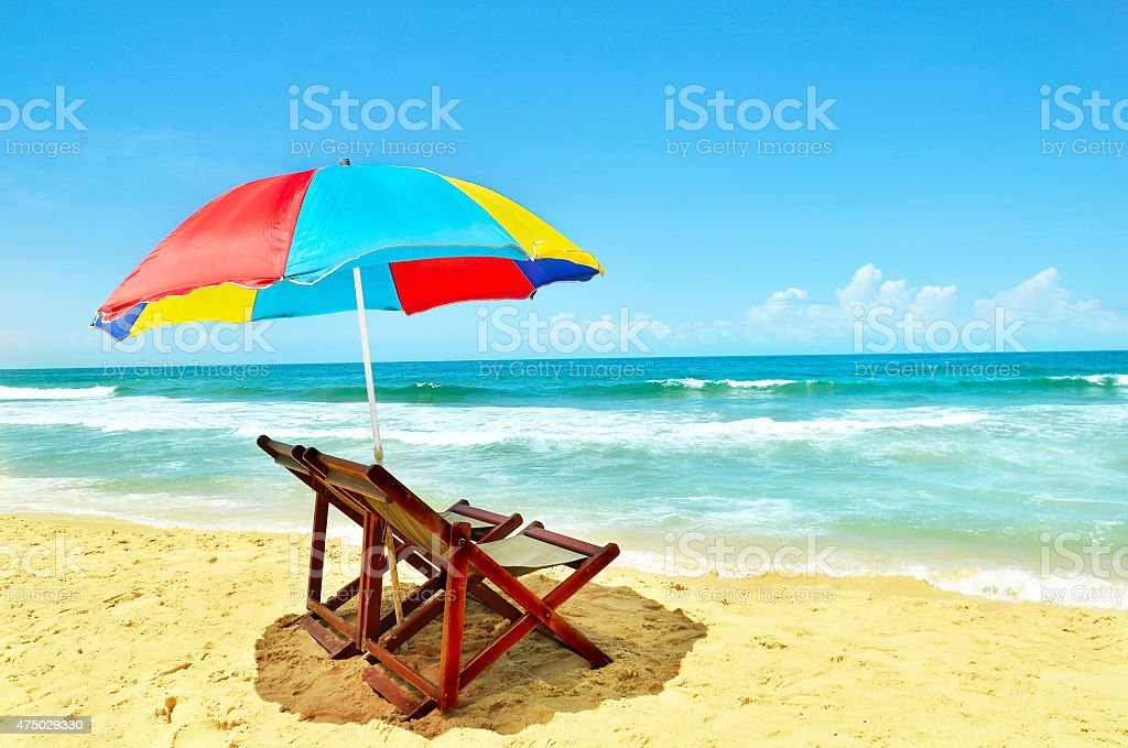 Summer at ocean beach with two chairs and umbrella stock photo