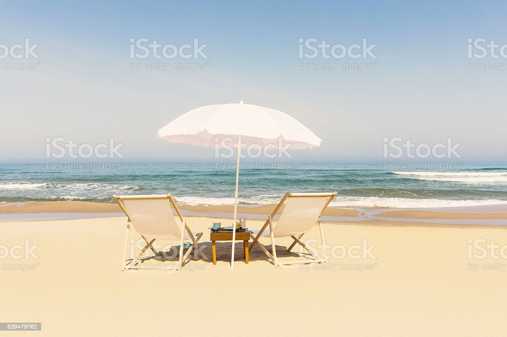Summer at Ocean Beach with Two Loungers and Umbrella stock photo