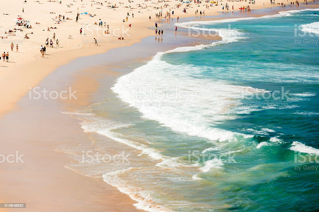 Summer at the beach and ocean with crowd of beachgoers stock photo