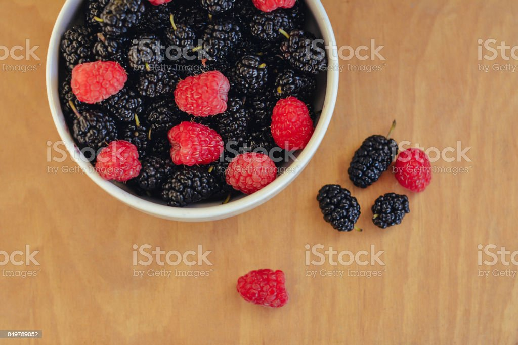 Summer berries in a pialat on wooden background stock photo