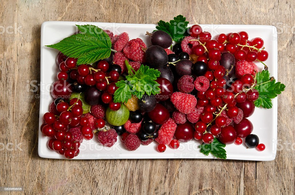 Summer berries in porcelain dish on wooden table stock photo