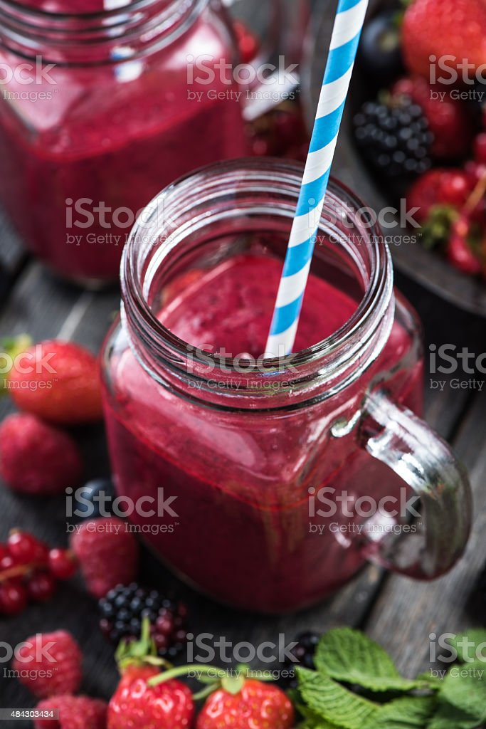 Summer berries smoothie in mason jar stock photo