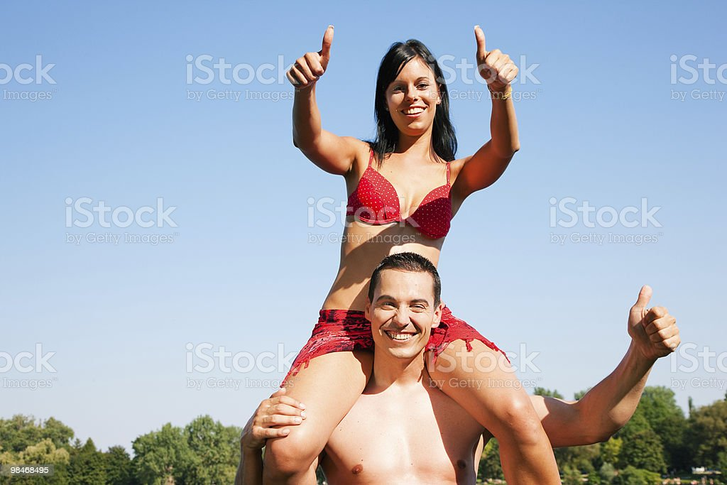Summer bikini girl sitting on shoulders of man royalty-free stock photo