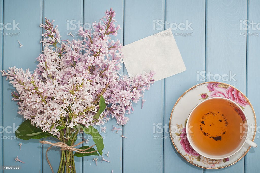 Summer bouquet of gentle blooming lilac with card and tea stock photo