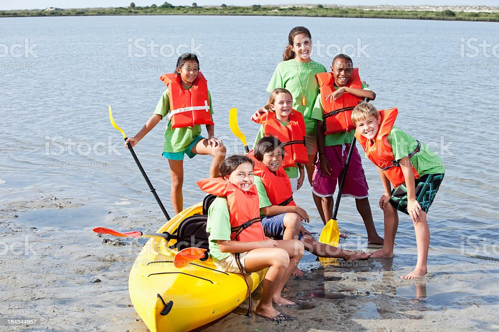 Summer camp counselor and children with kayak stock photo