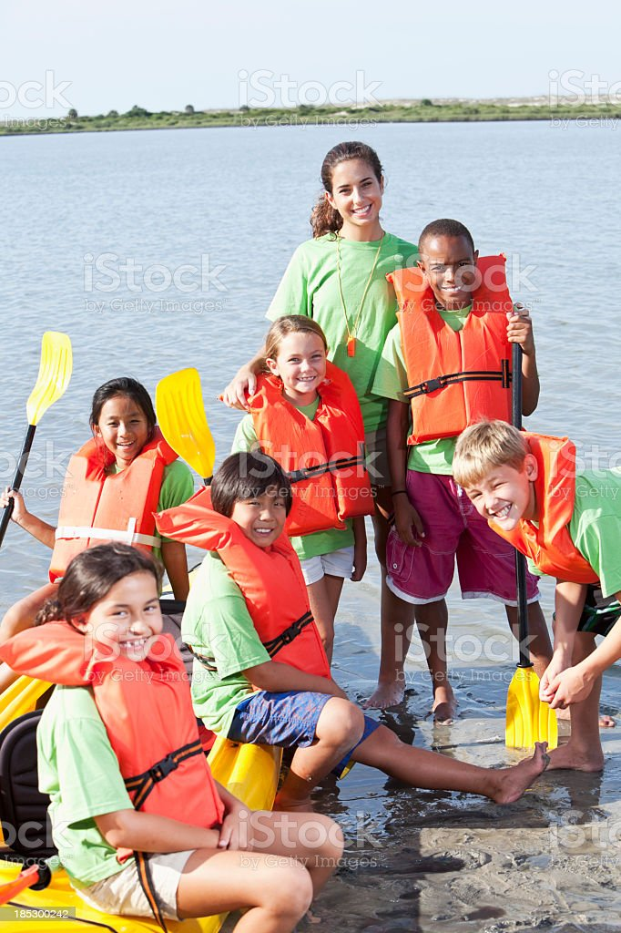 Summer camp counselor and children with kayak royalty-free stock photo