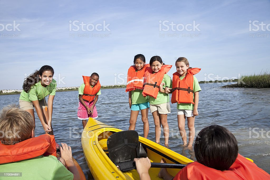 Summer camp counselor and children with kayaks stock photo