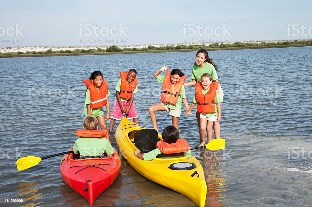 Summer camp counselor and children with kayaks royalty-free stock photo