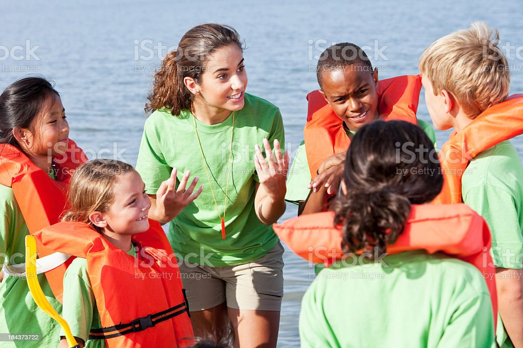 Summer camp counselor talking to children wearing life jackets stock photo