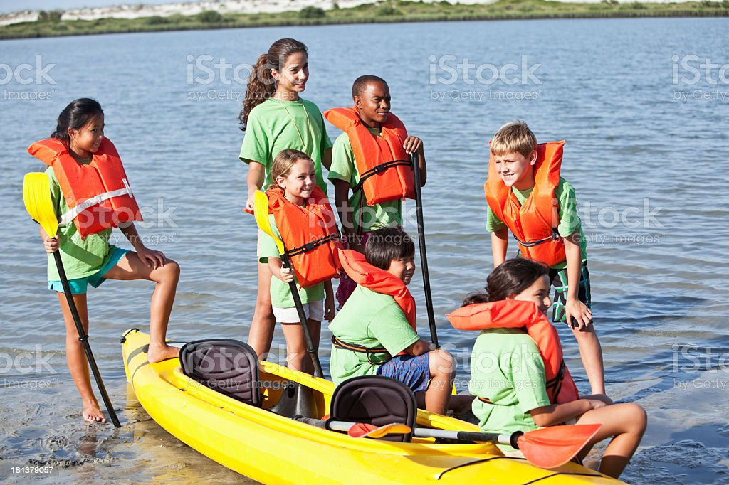 Summer camp counselor with children and kayak royalty-free stock photo